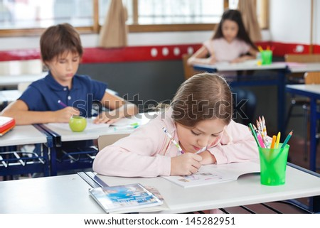 Little schoolgirl drawing while leaning on desk with friends in background at classroom