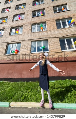 Little schoolgirl in front of the school decorated balloons - stock photo