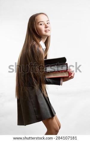 Little schoolgirl in uniform carrying heavy stack of books - stock photo