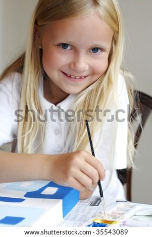 Little schoolgirl painting - stock photo