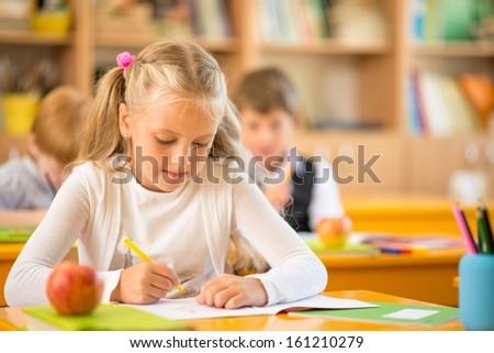 Little schoolgirl sitting behind school desk during lesson in school - stock photo
