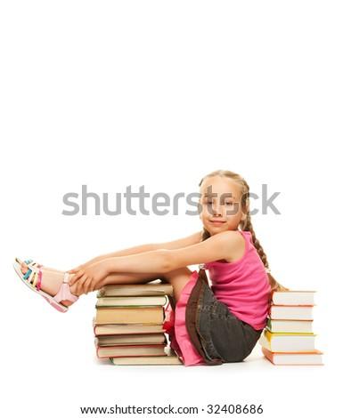 Little schoolgirl sitting between stacks of books - stock photo