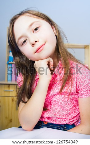 Little schoolgirl sitting on chair and holding a book - stock photo