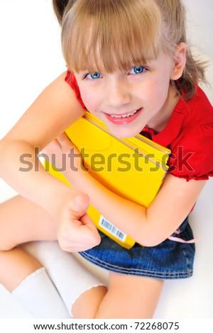 Little schoolgirl sitting with books - stock photo