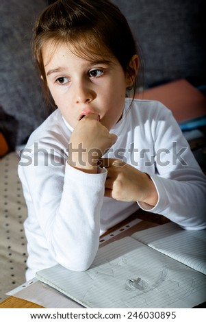 Little schoolgirl thinking about her homework - stock photo