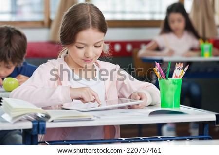 Little schoolgirl using digital tablet with classmates in background at classroom - stock photo