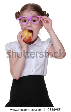 little schoolgirl with fresh organic red apple on healthlife theme