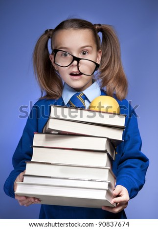 Little schoolgirl with glasses holding books - stock photo