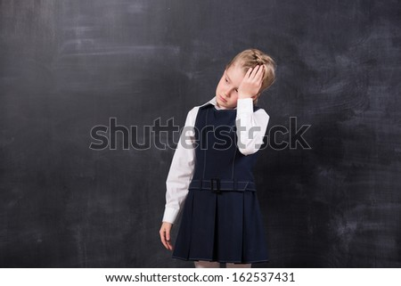 little schoolgirl with headache holding her head with hands stands at the blackboard - stock photo