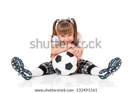 Little schoolgirl with soccer ball sitting on floor, isolated on white background