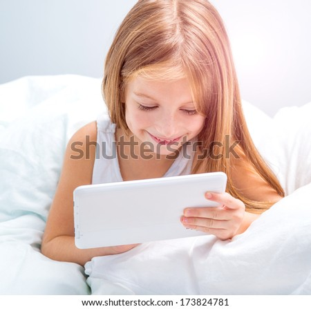 little schoolgirl with tablet lies in bed at home - stock photo