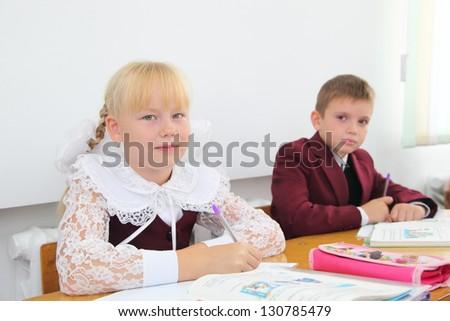 Little schoolgirl writes a pen in a notebook - stock photo