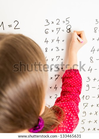 Little schoolgirl writing on blackboard - stock photo