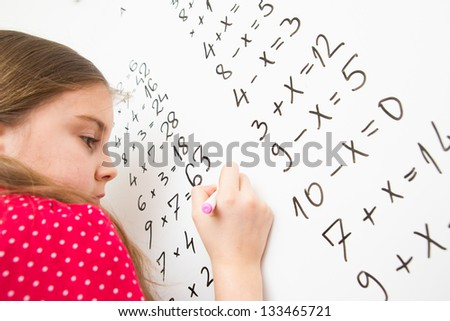Little schoolgirl writing on blackboard - stock photo