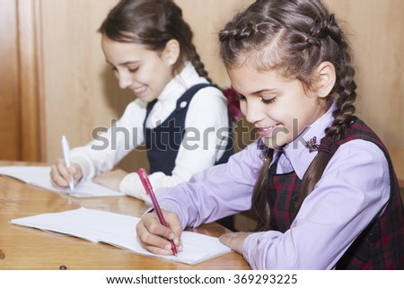 Little schoolgirl wrote in their notebooks in class