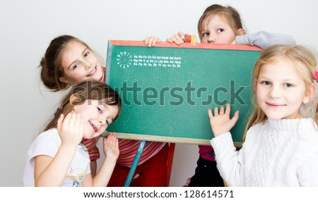 Little schoolgirls with blank blackboard - stock photo