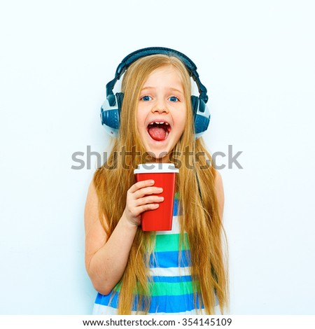 Little screaming girl standing against white background with red coffee cup, glass. Headphones on head. Isolated.