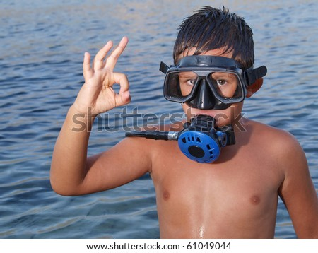 Little scuba diver giving an all ok sign before diving into beautiful blue adriatic sea - stock photo