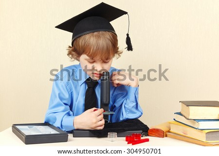 Little serious boy in academic hat looking through a microscope at his desk - stock photo