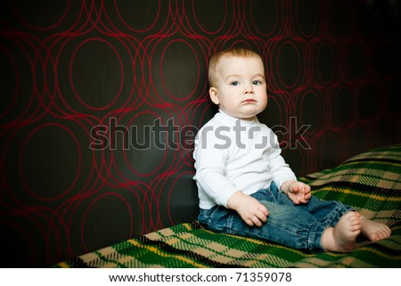 little serious boy sitting near the wall at home - stock photo