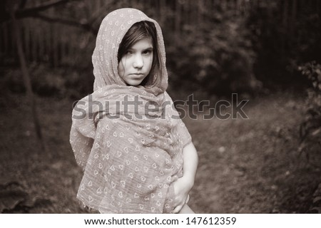 little serious preteen girl with red scarf and dark long hair black and white portrait - stock photo