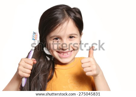 Little seven year old girl shows big smile showing missing top front teeth and holding a toothbrush on a white background
