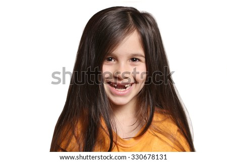Little seven year old, happy girl shows big smile showing missing top front teeth on a white background - stock photo