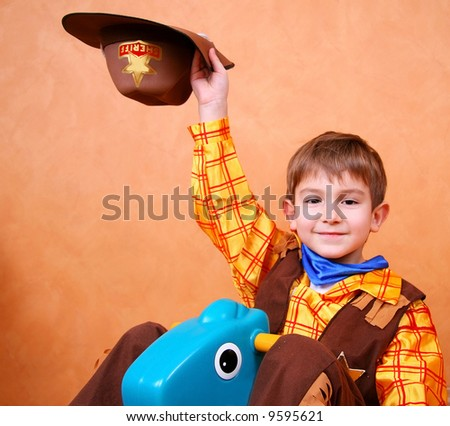 Little sheriff riding a pony - stock photo