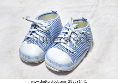 little shoes for baby in blue on white fabric.