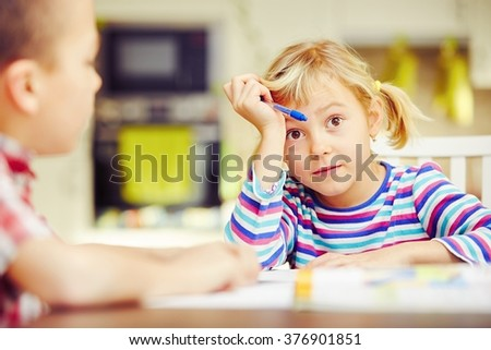 Little siblings are doing his homework for elementary school. - stock photo