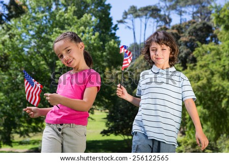 Little siblings waving american flag on a sunny day - stock photo