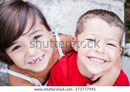 Little siblings with big smiles and missing milk teeth - stock photo