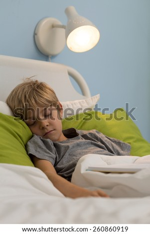 Little sick boy falling asleep in his hospital bed - stock photo