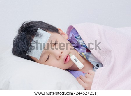 Little sick boy sleeping with digital thermometer in mouth  - stock photo