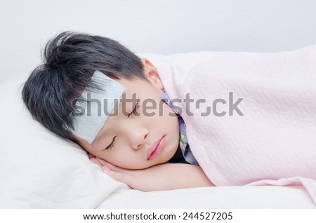 Little sick boy with cool gel sheet sleeping on bed - stock photo