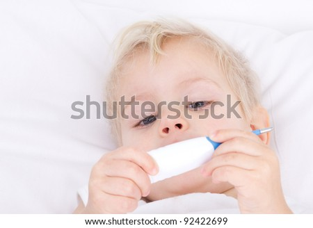 little sick girl in bed with thermometer in hands