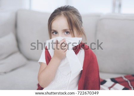 Little sick girl sits on a white couch wrapped in a red scarf. The girl is sitting on the couch and blows her nose in a white napkin. She is very ill