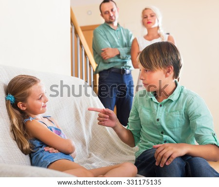 Little sister and brother abusing each other, parents standing near