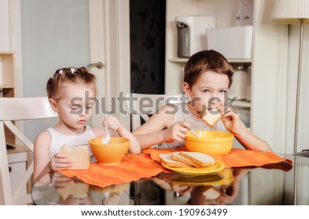 little sister and brother having dinner together - stock photo