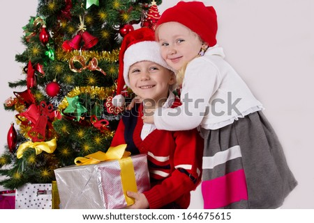Little sister and brother hugging under Christmas tree - stock photo