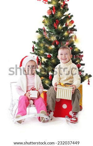 Little sister and brother with Christmas presents isolated on white