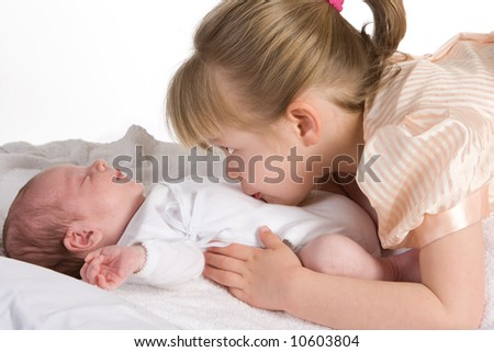 Little sister caressing her 15 days old brother - stock photo