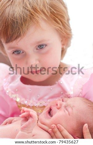 Little sister holding her 10 days old sister in hands.