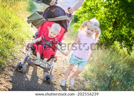 little sister holding the hand with her little sibling in  a stroller - stock photo