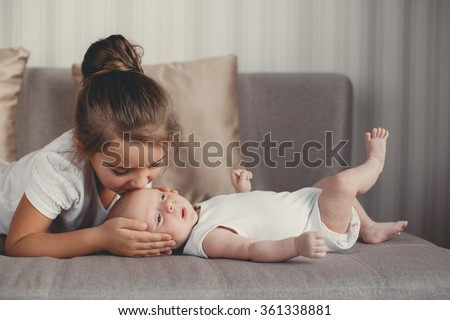Little sister hugging her newborn brother. Toddler kid meeting new sibling. Cute girl and new born baby boy relax in a white bedroom. Family with children at home. Love, trust and tenderness - stock photo