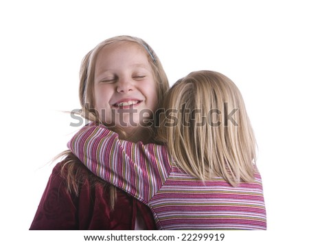 Little sister hugs big sister who is smiling with eyes closed - stock photo