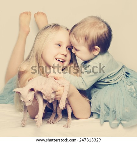Little sisters baby girl and kittens - stock photo