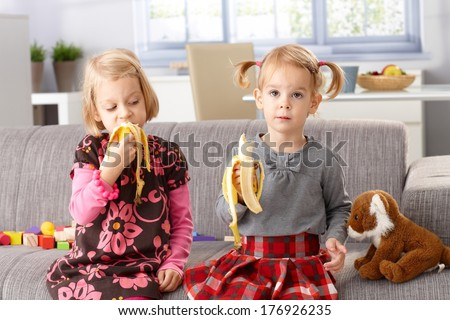 Little sisters eating banana at home, sitting on sofa.