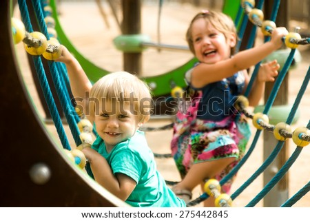 Little sisters having fun at action-oriented playground in park  - stock photo