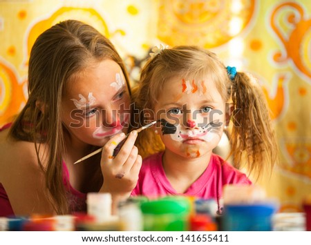 Little sisters playing with painting. - stock photo